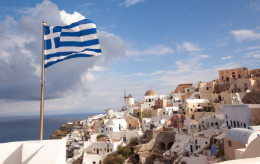 Greek flag waving in the village of Oia